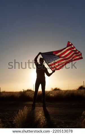 Young man proudly waving the American flag at sunset - stock photo