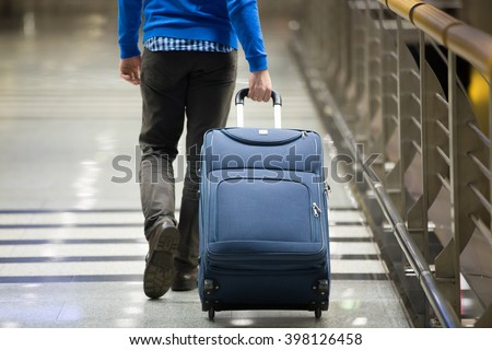 Young man pulling suitcase in modern airport terminal. Travelling guy wearing smart casual style clothes walking away with his luggage while waiting for transport. Rear view. Close-up - stock photo