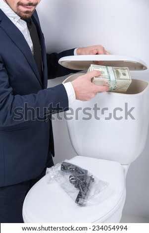 Young man pulls gun and money from the toilet tank. - stock photo