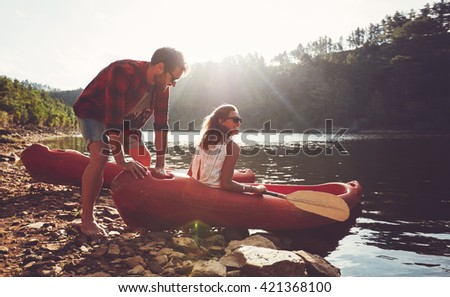 Young man pushes a canoe in the water while a woman sitting on the canoe. Couple going for kayaking in lake on a summer day. - stock photo