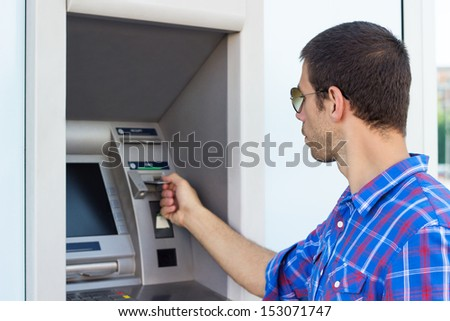 Young man put his credit card at the ATM