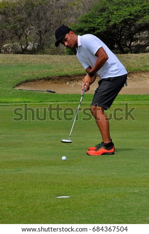 young man putting ball in hole at golf game
