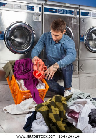 Young man putting dirty clothes in basket while sitting against washing machines at laundromat