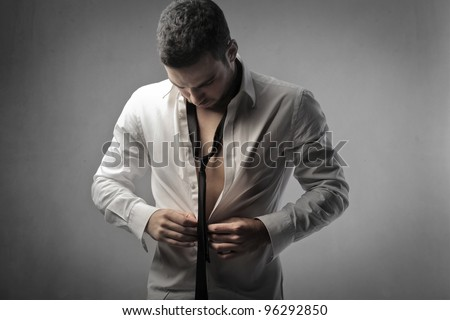 Young man putting on a shirt - stock photo