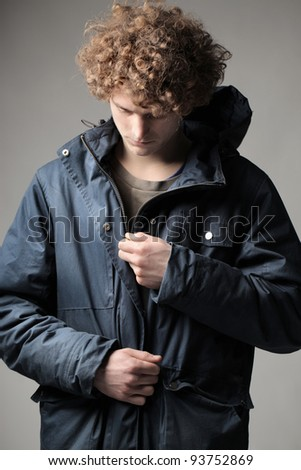 Young man putting on a windcheater - stock photo