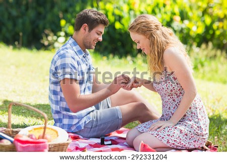 Young man putting on ring during marriage proposal on a sunny day - stock photo