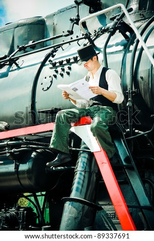 young man read a newspaper sitting on a locomotive - stock photo