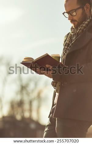 Young man reading a book and drinking coffee outdoor - stock photo