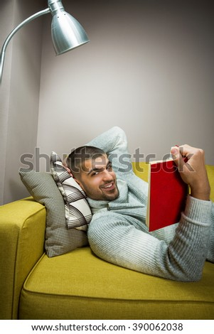 Young man reading a book at home. He lies on the sofa. - stock photo