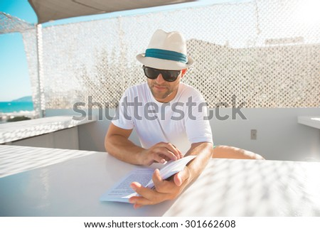 Young Man Reading a Book at seaside - stock photo