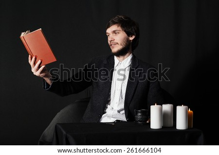 Young man reading a book by the table. Coffee, candles and enigmatic atmosphere.