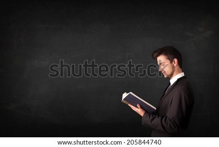Young man reading a book in front of a blackboard  - stock photo