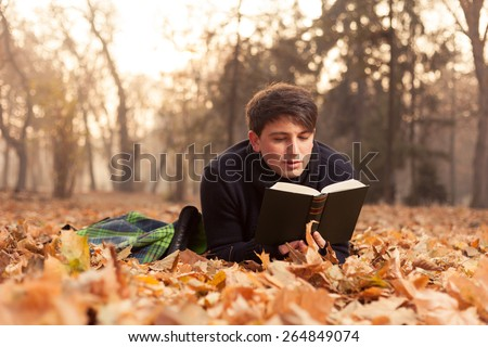 Young man reading a book in the autumn leaves  - stock photo