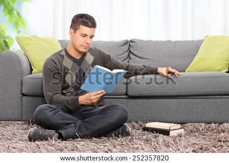 Young man reading a book seated on the floor at home  - stock photo