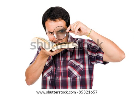 Young man reading a interesting book with magnifying glass, isolated on white - stock photo