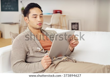 Young man reading an e-book on his tablet relaxing with his feet up on the couch with an engrossed expression