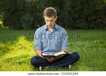 Young man reading Bible in a park - stock photo