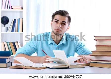 Young man reading book at table in room