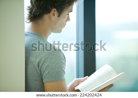 Young man reading book by window, side view - stock photo