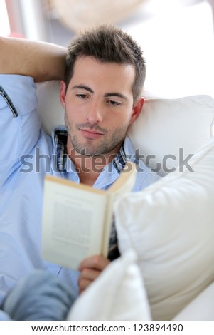 young man reading book in sofa - stock photo