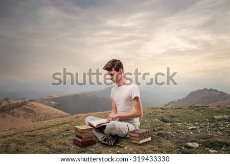 Young man reading books while sitting in the mountains - stock photo