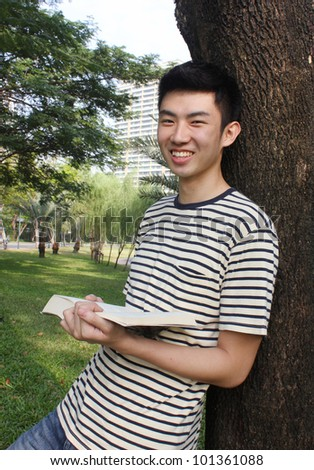 Young man reading in the park - stock photo