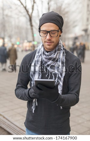 Young man reading messages and information using an i-pad tablet computer.