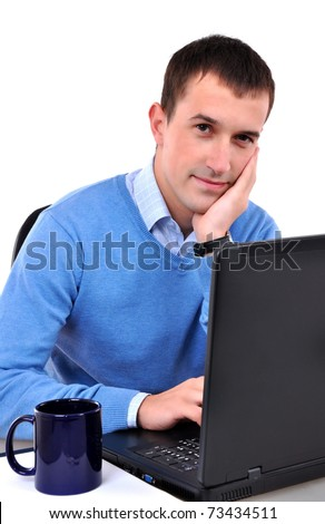 Young man reading on laptop, drinking tea or coffee - stock photo
