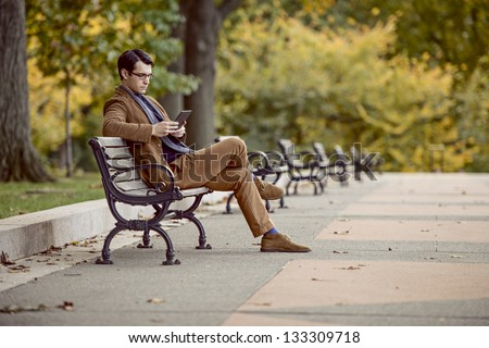 Young Man Reading With A Digital Tablet At The Park - stock photo