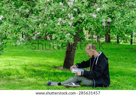 Young man reads a book under blooming apple tree