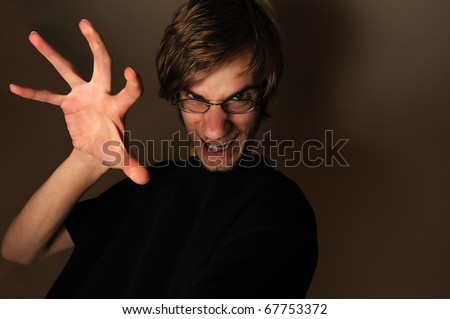 Young man ready to grab, touch, or snatch something with his large hand claw. He looks like a techie with his glasses and braces on, but can qualify as any sort of regular person being scary.