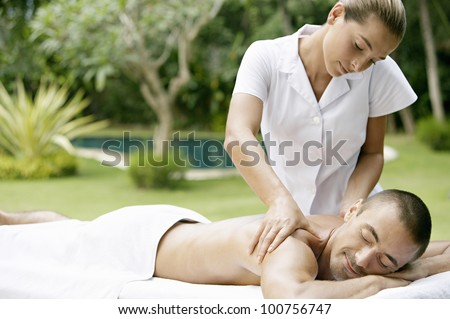 Young man receiving a massage in a tropical garden near a swimming pool.