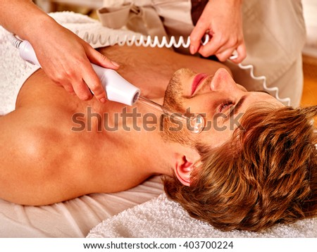 Young man receiving electric darsonval facial massage after procedure at beauty salon. Close up. - stock photo
