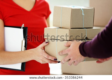 Young man receiving parcel from delivery worker, close up - stock photo