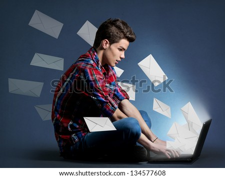 Young man receiving tons of messages on laptop, communication concept - stock photo