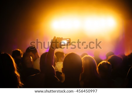 Young man recording concert at party