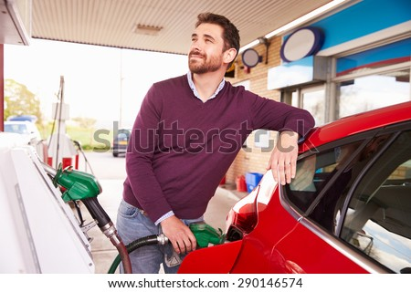 Young man refuelling a car at a petrol station - stock photo