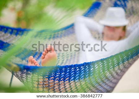 Young man relax in hammock at exotic tropical vacation