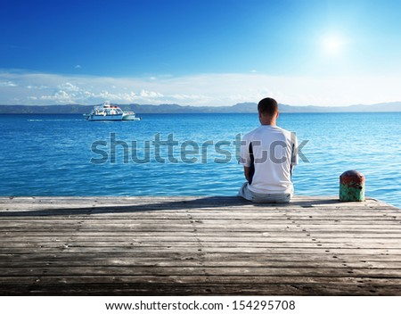 young man relax siting on pier  - stock photo