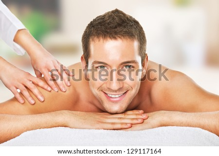 Young man relaxed in spa / Closeup of a man having a back massage - stock photo