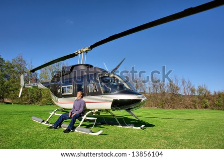 Young man relaxes next to small private helicopter on grass in estate. Shot  near Cape Town, Western Cape, South Africa.