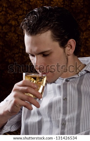 Young man relaxing after a hard day with a drink.