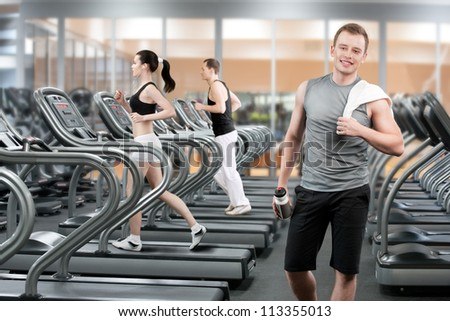 Young man relaxing after running in fitness club