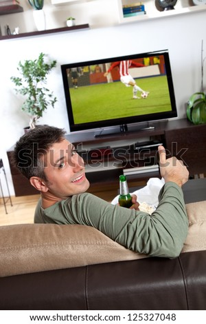 Young man relaxing and enjoying watching TV at home - stock photo