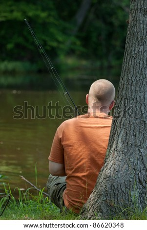 Young man relaxing and fishing on a lake in Virginia. - stock photo