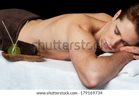 Young man relaxing at the spa ready to get a massage - stock photo
