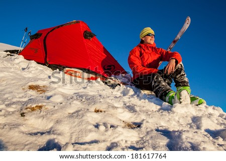 Young man relaxing in front of a tent in winter - stock photo