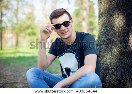 Young man relaxing in the park on a summers day