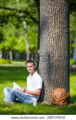 Young man relaxing near tree with coffee reading a book - stock photo