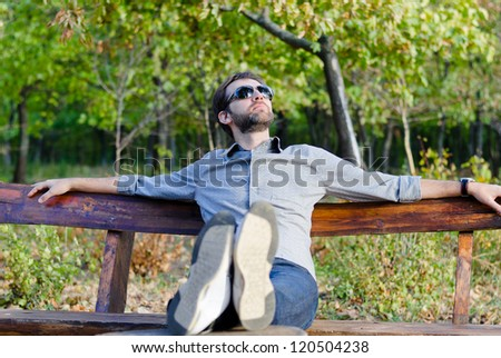 Young man relaxing on a park bench with his feet up and head thrown back looking at the sun - stock photo